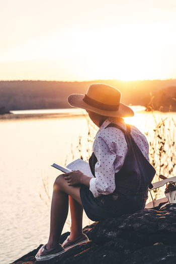 Nature Outdoors Lifestyles Women Landscape Education Book Sunlight Water Holiday People Hat Sky One Person Sunset Beauty In Nature Reading Reading A Book