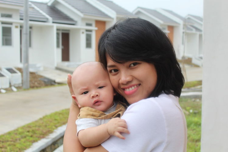 Portrait of smiling mother and cute son outside house