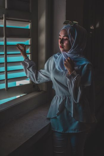 Woman Wearing Hijab While Looking Through Window