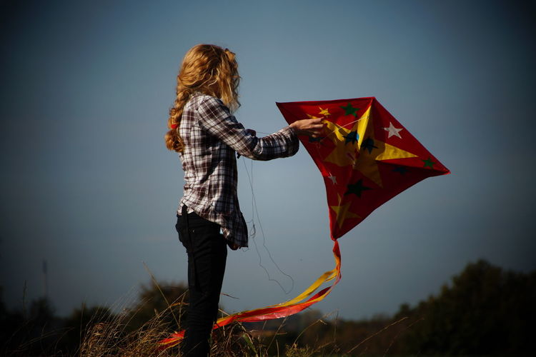Woman holding kite while standing on field
