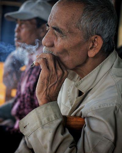 Close-up of senior smoking cigarette by man