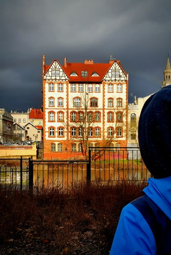 Rear View Of Person Looking At Residential Building Against Cloudy Sky
