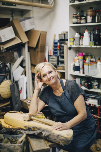 Portrait of confident female upholstery worker sitting at workbench in workshop
