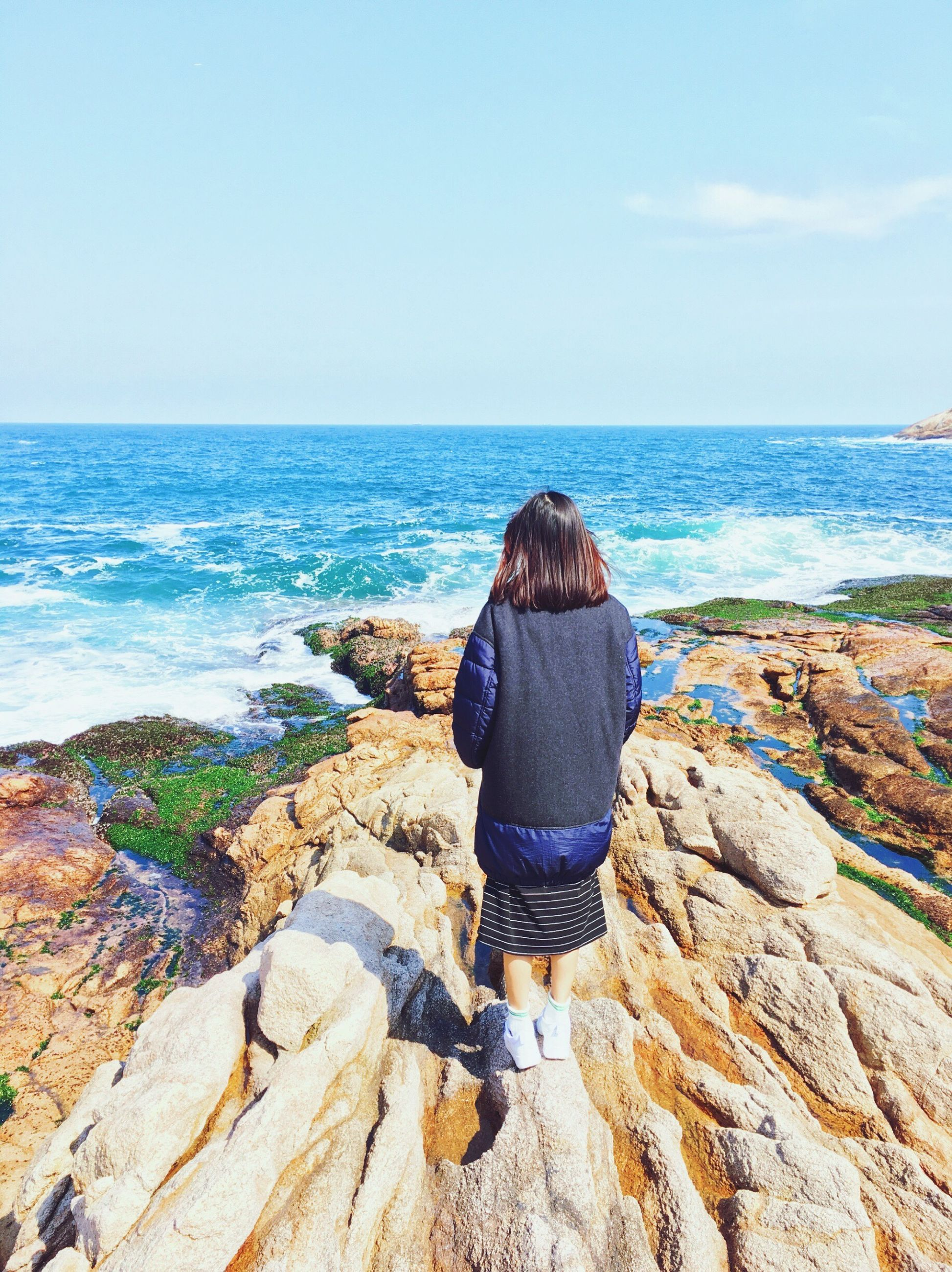 sea, horizon over water, rear view, lifestyles, water, leisure activity, standing, full length, beauty in nature, scenics, rock - object, tranquility, beach, tranquil scene, nature, casual clothing, sky, shore