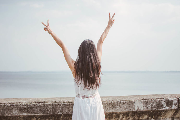 Happy Adult Arms Raised Beauty In Nature Day Horizon Over Water Leisure Activity Lifestyles Long Hair Nature One Person Outdoors People Real People Rear View Sea Sky Standing Water Women Young Adult Young Women