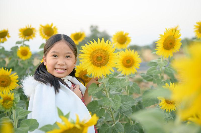 Portrait of smiling girl amidst sunflower field against sky