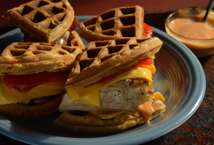 Chicken and savory waffle sandwiches with cheddar cheese, roasted red peppers, aioli sauce