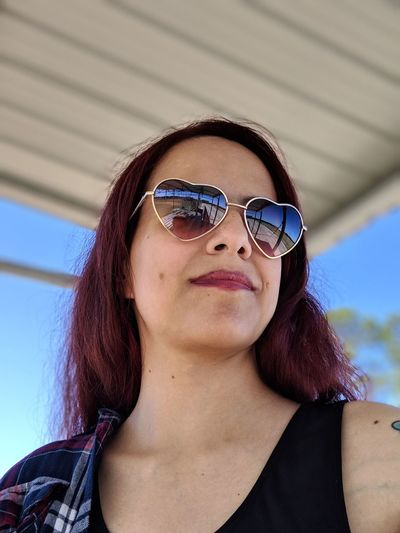 Low angle view of young woman wearing sunglasses looking away