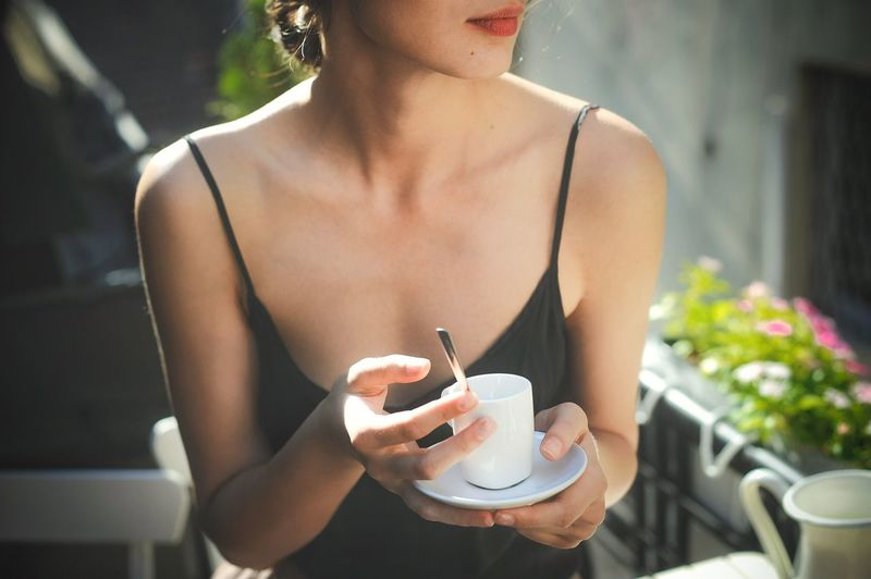 Midsection Of Woman Holding Coffee While Sitting Outdoors