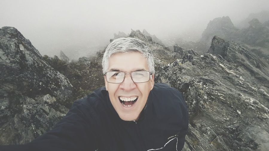 Portrait Of Smiling Man Standing On Rock Against Sky