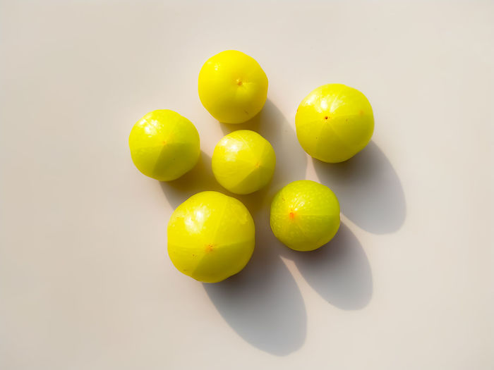 High angle view of yellow balls on white background