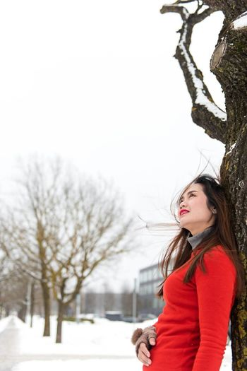 Woman Leaning On Tree Against Sky During Winter
