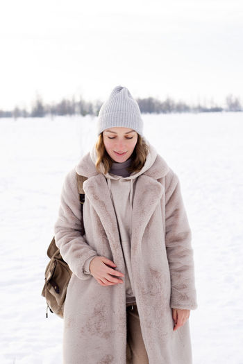 Woman wearing hat standing in snow