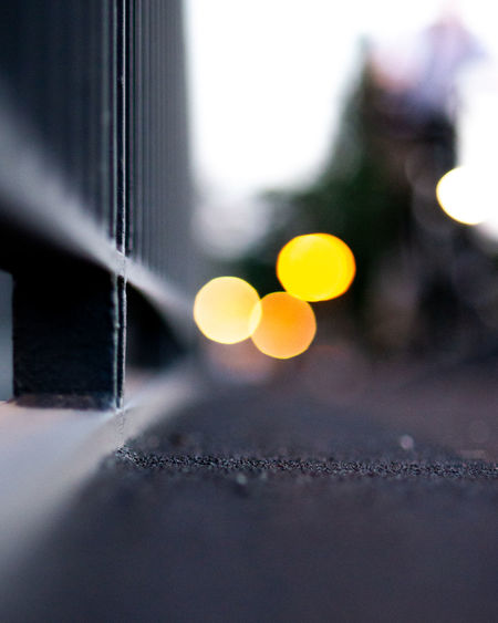 Close-up of yellow lights on railing by street