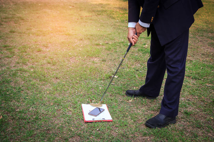 Low Section Of Businessman With Golf Club Hitting Smart Phone On Grassy Field