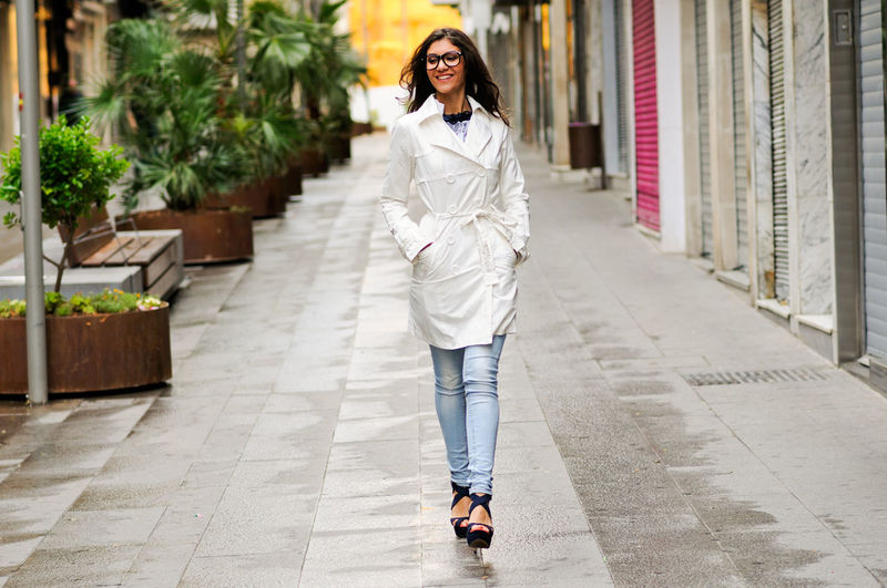 Cheerful Young Woman Walking On Footpath In City