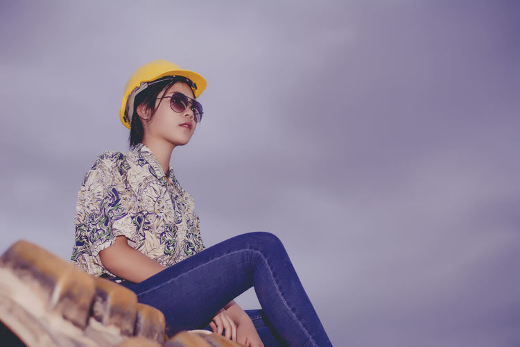 Low angle view of young woman wearing hardhat while sitting against cloudy sky