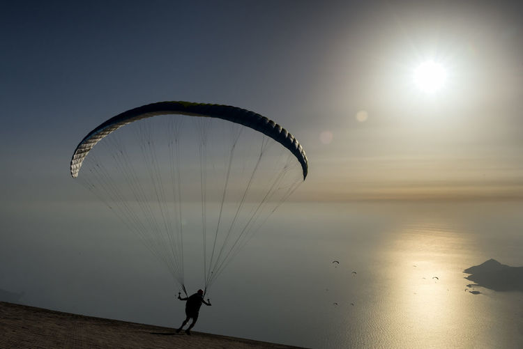 Silhouette of person paragliding at sunset