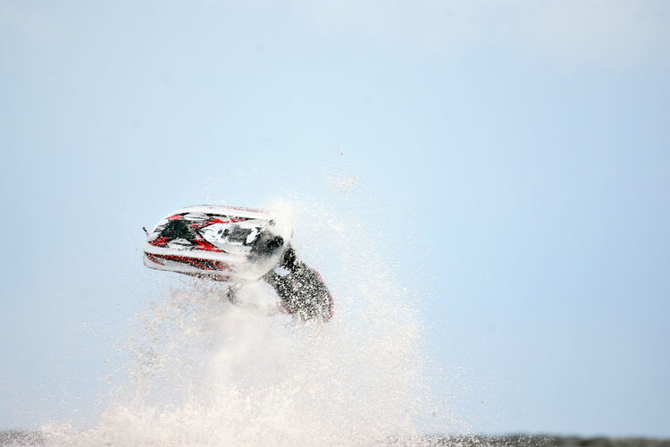 Man performing stunt with jet boat against sky