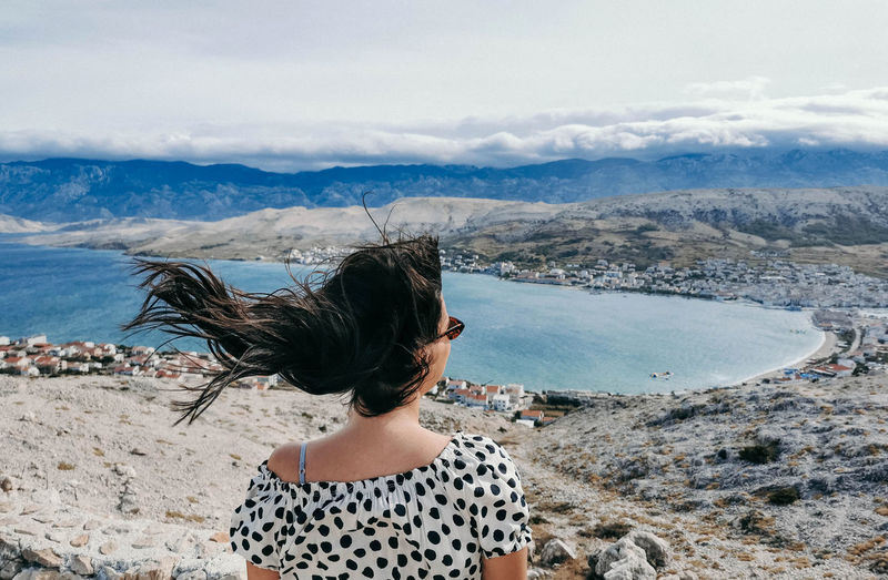 Rear view of young woman on viewpoint over sea. wind blowing hair.