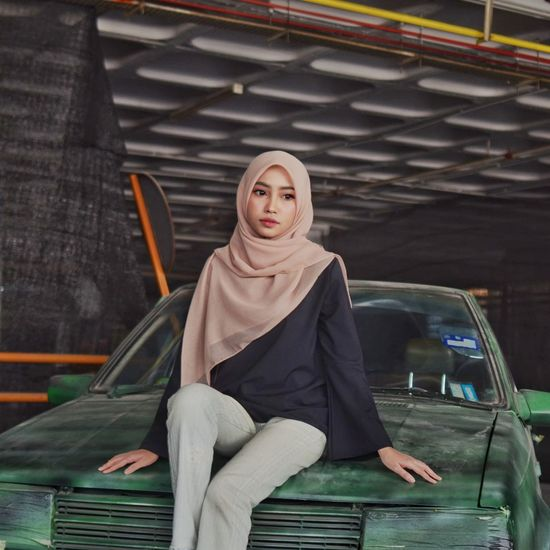 Thoughtful beautiful young woman in hijab sitting on old car