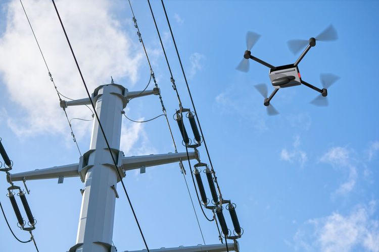 Low angle view of drone flying by electricity pylon against sky