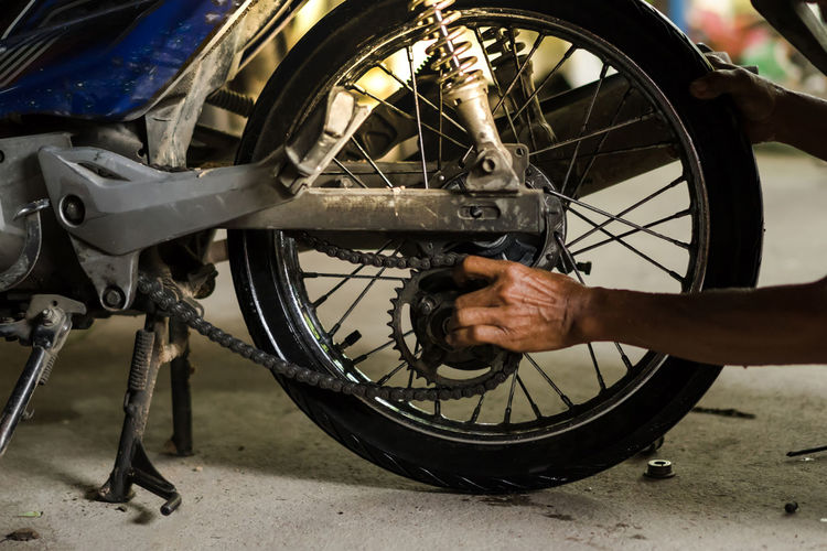 A man fix broken motorcycle Wheel Transportation Bicycle Tire Mode Of Transportation One Person Land Vehicle Real People Day Outdoors Spoke Human Body Part Travel Focus On Foreground Close-up Stationary City Holding Metal Mechanic