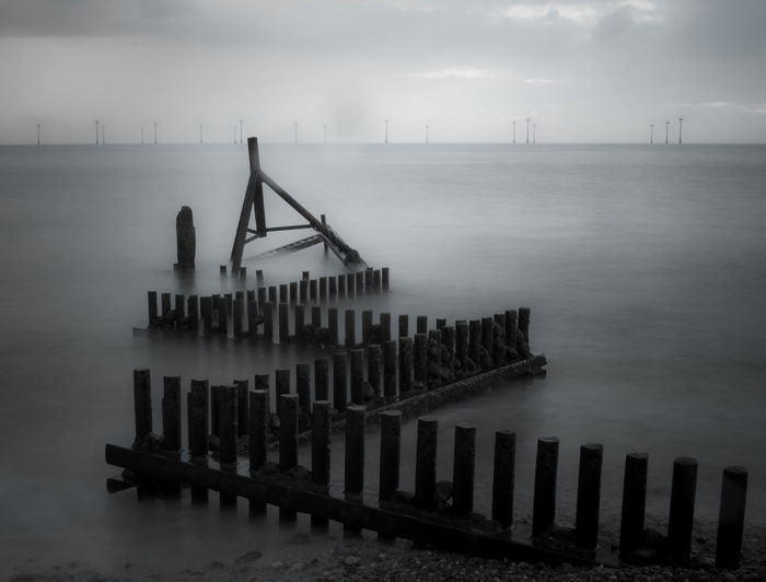 High angle view of wooden posts in sea during foggy weather