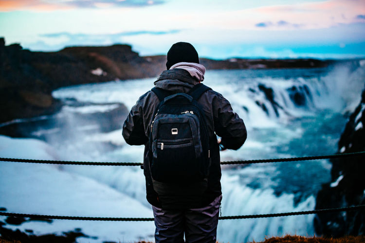 Camera - Photographic Equipment Casual Clothing Cloud Cloud - Sky Focus On Foreground Iceland Island Leisure Activity Lifestyles Looking At View Men Photographing Photography Themes Railing Rear View Sky Standing Technology Three Quarter Length Water
