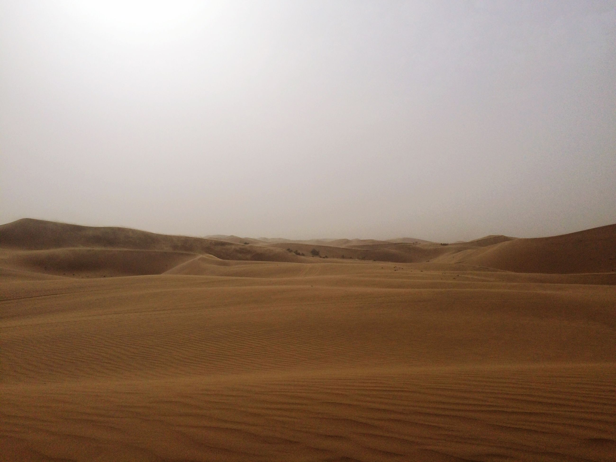 sand, tranquility, tranquil scene, landscape, scenics, copy space, beauty in nature, desert, nature, sand dune, remote, clear sky, arid climate, non-urban scene, idyllic, travel destinations, wave pattern, outdoors, sky, horizon over land, extreme terrain, surface level, no people