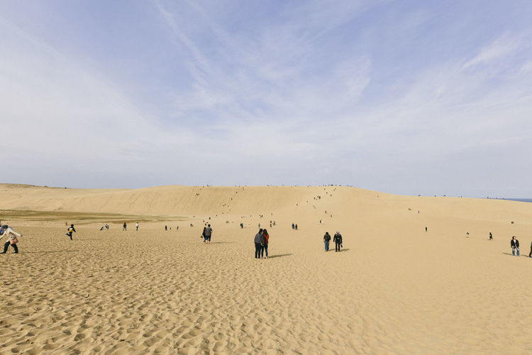 Group of people on desert against sky