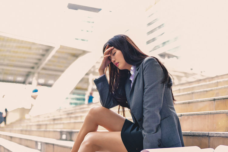 Businesswoman Suffering From Headache On Steps