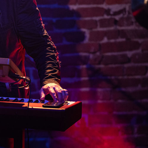 Midsection man playing piano on stage at night