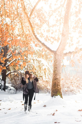 Full length of woman standing in forest during winter