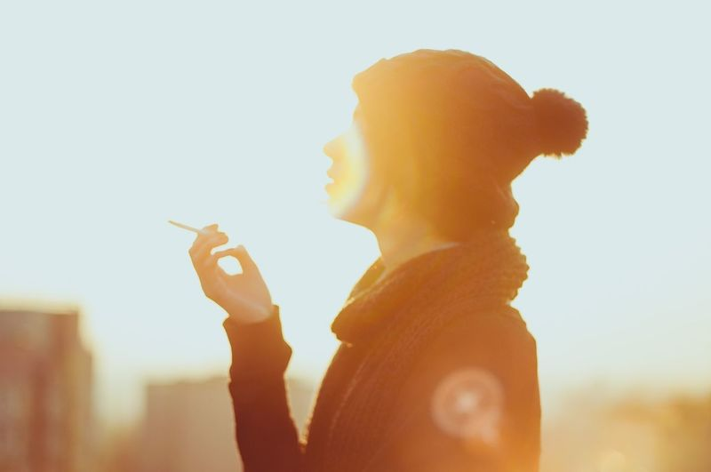 Close-up of young woman smoking cigarette against sky