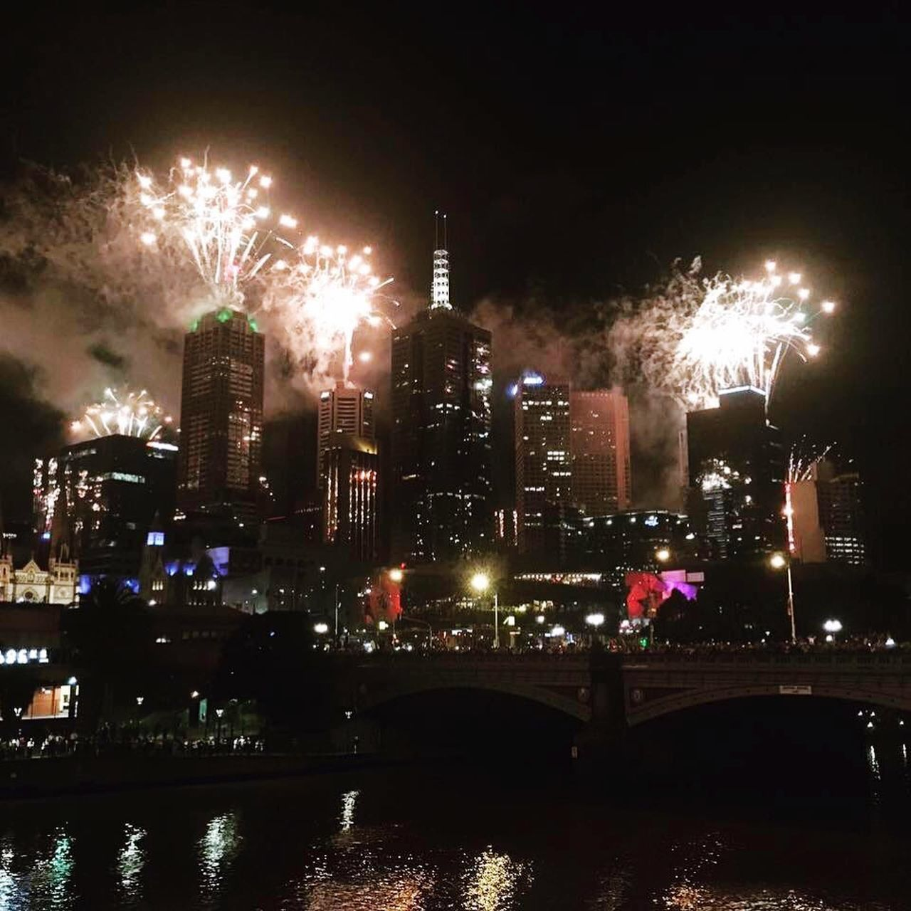 night, architecture, building exterior, built structure, illuminated, city, building, sky, office building exterior, cityscape, firework, no people, skyscraper, firework display, motion, water, exploding, arts culture and entertainment, river, celebration, outdoors, firework - man made object, light