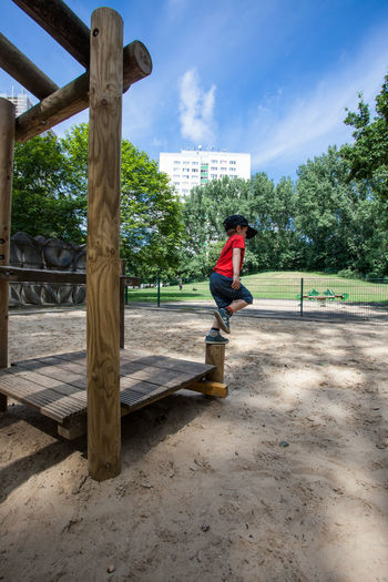 Full length of boy on wooden play equipment at park