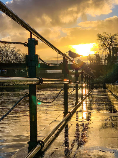 Wet bridge over river against sky during sunset