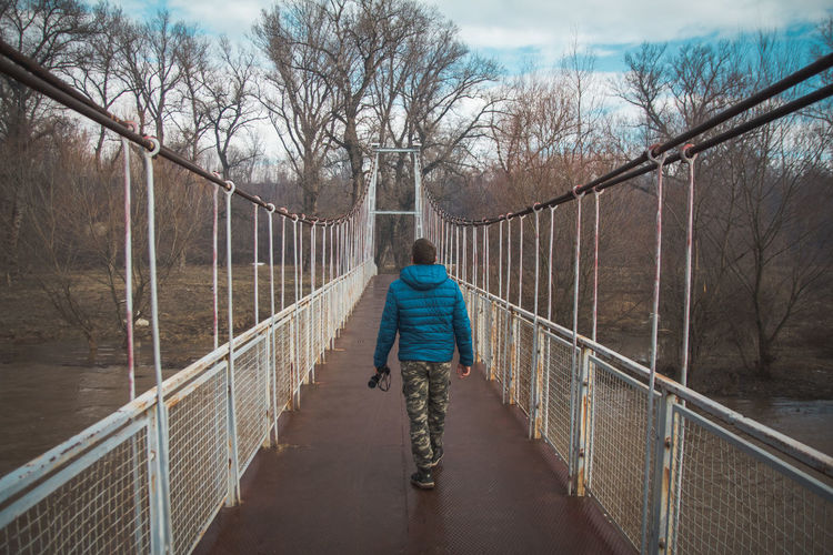 Young man crossing a bridge in the forest. Birdwatching Real People Full Length Tree Railing One Person Rear View The Way Forward Direction Lifestyles Bridge Day Casual Clothing Leisure Activity Nature Bridge - Man Made Structure Footbridge Motion Outdoors Riding Hairstyle EyeEmNewHere Autumn Binoculars Birdwatching 17.62° My Best Photo