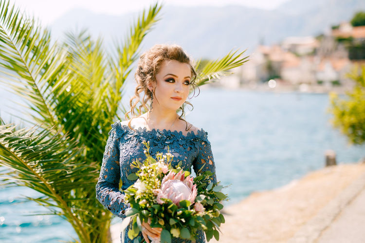 Bride holding bouquet while standing against sea