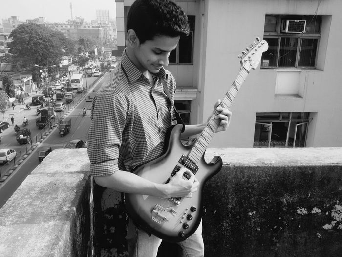 Young Man Playing Guitar While Standing On Terrace