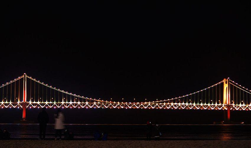 Illuminated gwangan bridge against clear sky at night