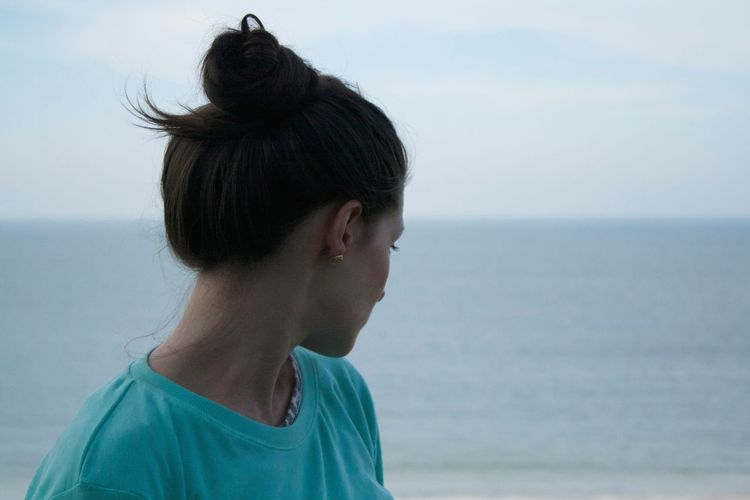 Close-up of young woman against sea