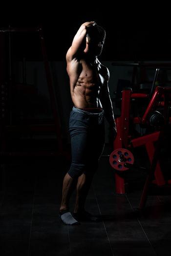 Full length of shirtless man standing on tiled floor