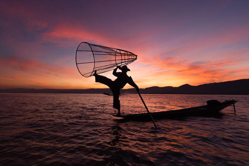 Silhouette man fishing net on lake at sunset