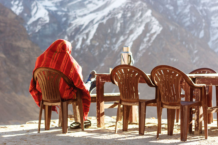 Rear view of man sitting on chair against snowcapped mountain