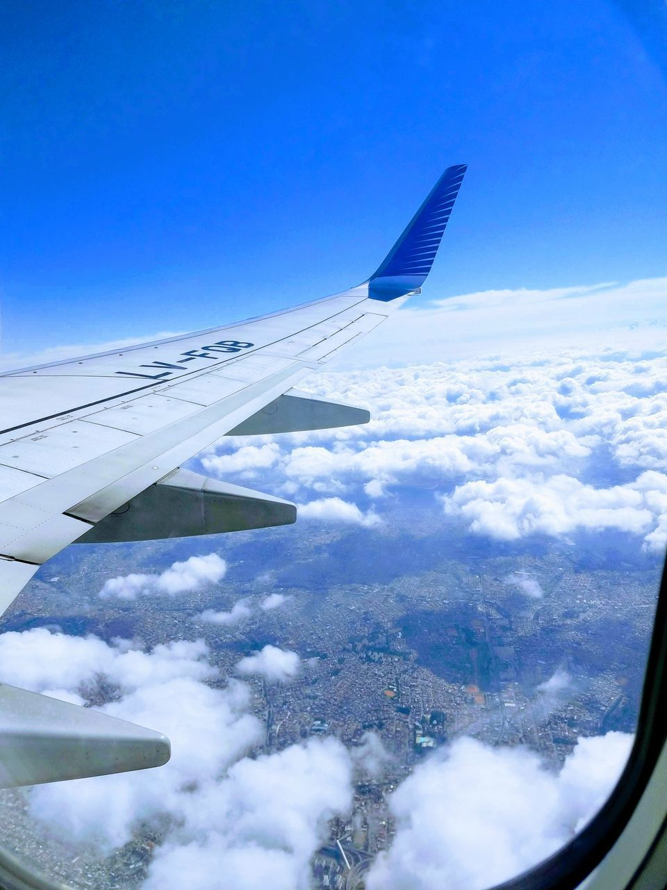 AERIAL VIEW OF AIRPLANE WING OVER CLOUDS