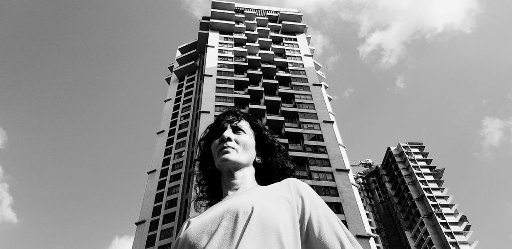 Low angle view of statue against modern building against sky