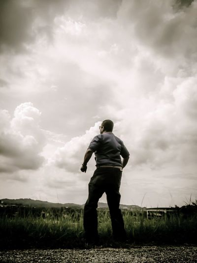 Rear view of man standing on field against clouds