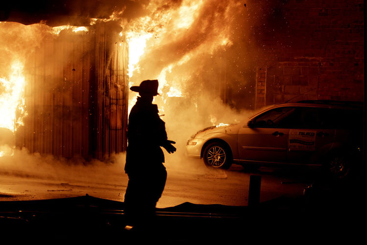 A fireman walks by a fire at a downtown building in Carterville, Illinois. Burning Burning Building Car Car On Fire Downtown Fire Emergency Emt Fire Fireman Men Night Silhouette Spot News